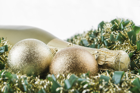 Holiday concept. Bottle of champagne and christmas decorations on garlands with white background.