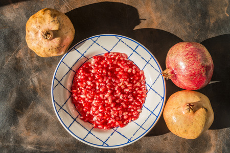 Healthy food concept. Still life with pomegranates and dish with red pomegranate grains on wooden table. Banque d'images - 121793200
