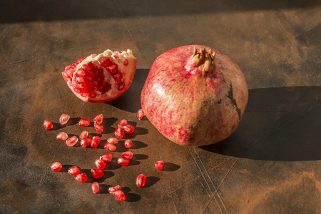 Healthy food concept. Still life with a pomegranates with some grains on wooden table.