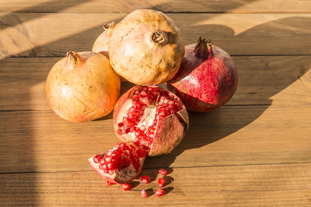 Healthy food concept. Still life with pomegranates on wooden table. Banque d'images - 121793224
