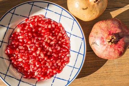 Healthy food concept. Still life with pomegranates and dish with red pomegranate grains on wooden table. Banque d'images - 121793241