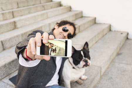 Lifestyle concept. Man making a selfie with his dog.