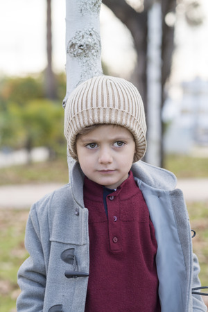 Boy posing with wool hat and warm clothes in a park.