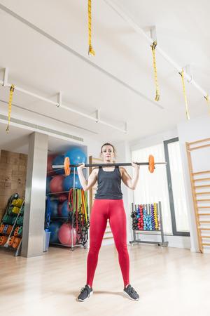 Femme d'âge moyen (40-45 ans) pratiquant le fitness dans une salle de sport.