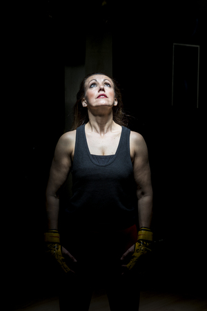 Portrait of a woman with boxing gloves on black background and illuminated with overhead light. Banco de Imagens