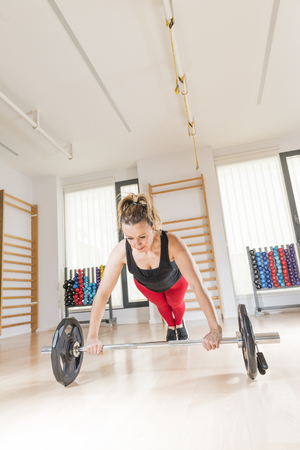 Middle-aged woman (40-45 years old) practicing fitness in a gym.