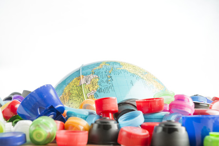 Conceptual and metaphorical photograph of a globe buried in plastic stoppers. Banco de Imagens