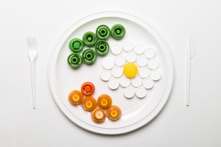Conceptual and metaphorical photography of a plate with food made with plastic stoppers. Banco de Imagens