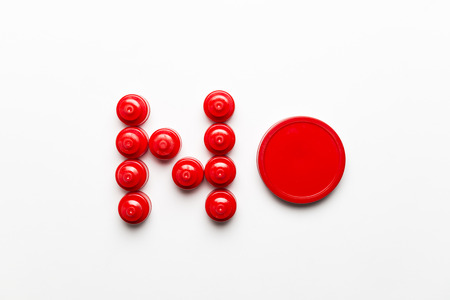 Conceptual photo of red plastic stoppers forming the word NO, on a white background. Banco de Imagens