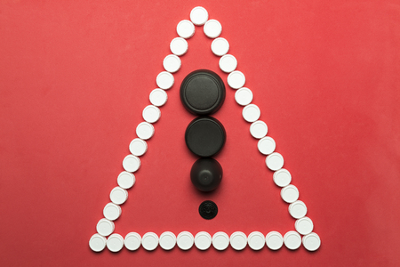 Conceptual and metaphorical photograph of a warning sign made with plastic stoppers on a red background.