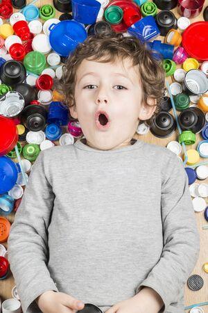 Fotografia concettuale sull'uso della plastica. Bambino sdraiato sul pavimento circondato da tappi di plastica.
