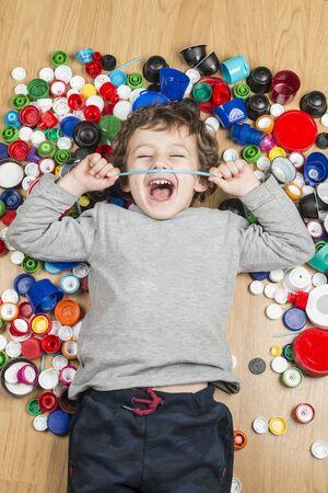 Fotografía conceptual sobre el uso de plásticos. Niño tirado en el suelo rodeado de tapones de plástico.