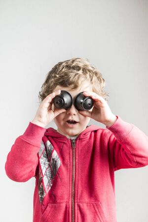 A child playing with coffee capsules using them as binoculars. Conceptual photography that tries to represent the recycling of plastic material.