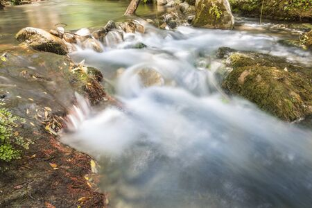 Mountain stream of clean and clear waters that flows between the rocks through the forest. Majaceite River in its transit through the Sierra de Grazalema, Spain. Concepts of purity and environment. Foto de archivo