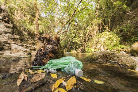 Basura en una bolsa de plástico abandonada en la orilla de un río de agua limpia. Conceptos de daño ambiental y reciclaje de envases plásticos.