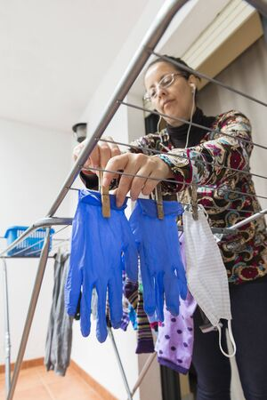 Woman hanging a homemade face mask and rubber gloves. Photograph showing the need to reuse the protection material against the covid-19 due to the scarcity of them. Stock Photo