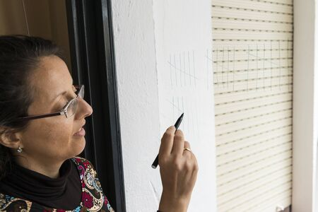 Woman drawing lines on the glass of a window to count the days.