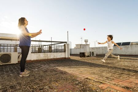 A woman and a child playing ball on a rooftop on a sunny day. Foto de archivo
