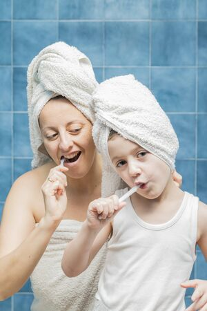 A woman and a boy with towels on their heads brushing their teeth.