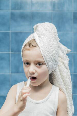 A child with towels on his head brushing his teeth. Banque d'images
