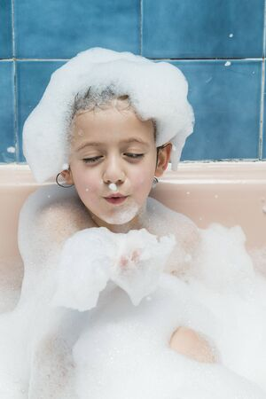 Portrait of a boy in a bathtub with foam, blowing foam from his hands. Archivio Fotografico