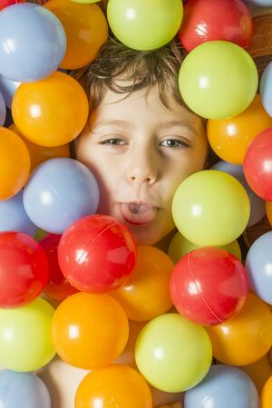 Creative portrait of a boy with his face surrounded by colored balls.