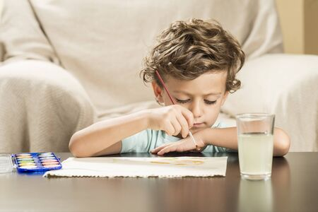 Child painting with watercolors on paper. Concepts back to school and childhood.
