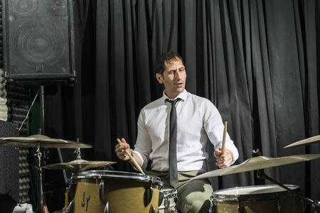 Man playing the drums at a rehearsal venue