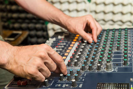 Music concept. Detail of the hands of a man manipulating a mixing desk.