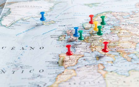 Thumbtacks pinned to a map of Europe. Travel conceptual photography.