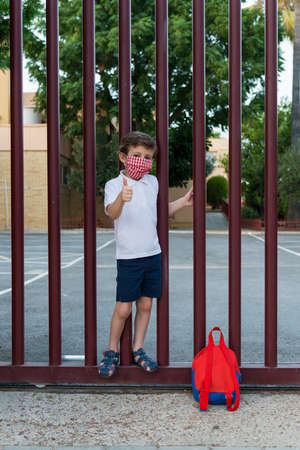 Portrait of a school boy with a face mask at the door of a school. Concept of the new normal in school during the Covid19 pandemic. Banco de Imagens