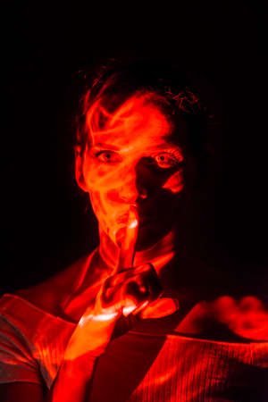Creative portrait of a woman illuminated with a red light with her index finger on her mouth to express silence, on black background. Archivio Fotografico