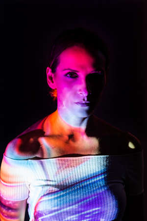 Creative portrait of a woman illuminated with colored lights on dark background.