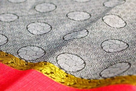 A close shot of the fabric of a saree to reveal the pattern on it