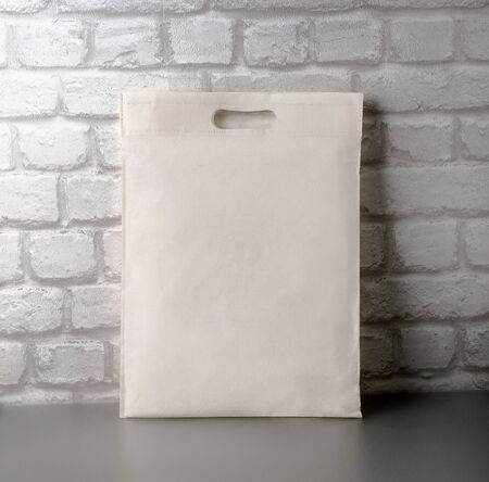 An empty, clean cloth bag against a brick wall. Layout for your ad. Stylized stock photos. Banner