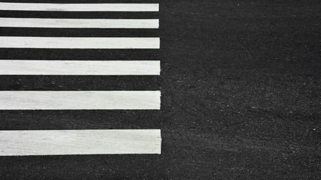 Zebra crosswalk on a asphalt road - closeup background Фото со стока