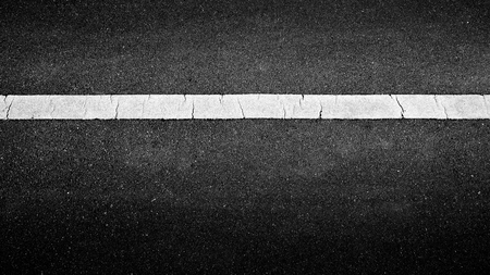 white paint line on black asphalt. space transportation background Foto de archivo