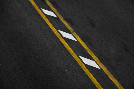 Yellow and white paint line on black asphalt. space transportation background Stock Photo