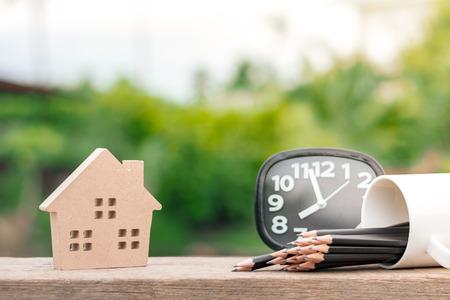 Braunes Holzhaus-Symbol auf Holzschreibtisch am Morgen. Für Immobilienhintergrund. Standard-Bild