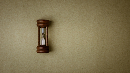 old hourglass on old brown recycled paper background Stock Photo