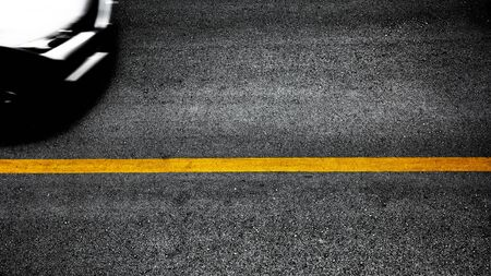 Yellow paint line on black asphalt. space transportation background