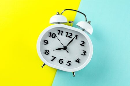 white vintage alarm clock on yellow and blue background. - top view. Stock Photo