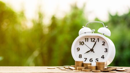 Retro alarm clock and a pile of golden coins on the table. - Concept of opportunity cost time and Money saving. Stock Photo - 125025060