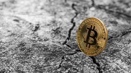 Shiny golden bitcoin on cracked floor.
