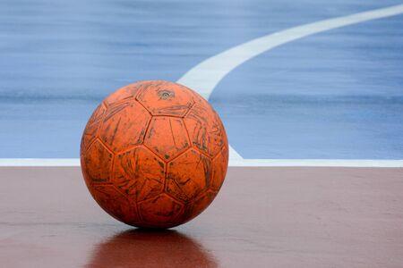 old and damaged orange ball at futsal court Stockfoto - 125033124