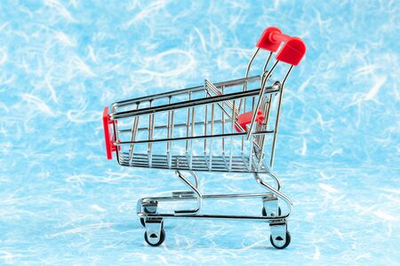 empty shopping cart on blue background. - for advertising and for copy space.