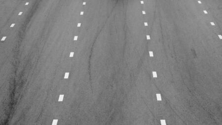 white paint line on black asphalt. space transportation background Stock Photo