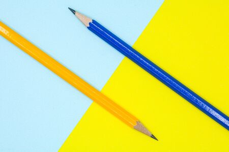 yellow and blue pencil on a blue and yellow paper - background
