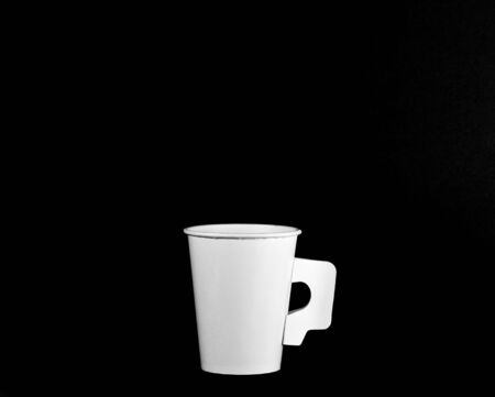 White paper coffee cup isolated on black background - close up