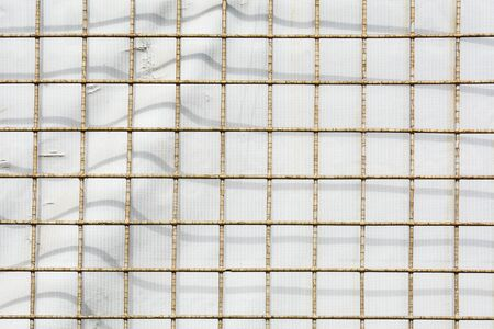 old and rusty cage metal net and the shadow at a white canvas - background